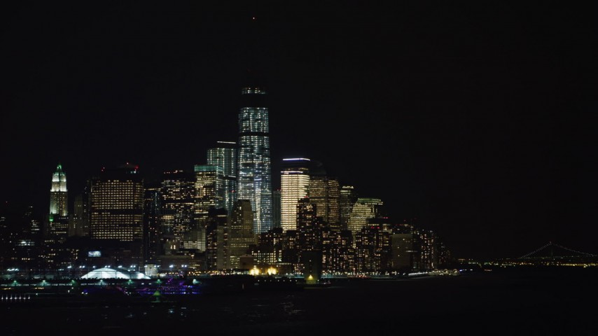 4K stock video aerial view of World Trade Center skyscrapers seen from the Hudson River at night, New York City Aerial Stock Footage | AX67_0065
