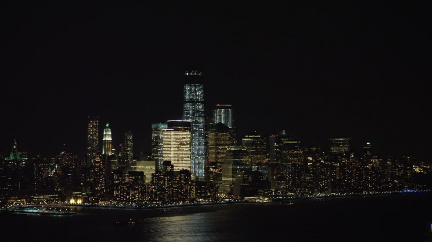 4K stock video aerial view of World Trade Center skyscrapers seen from New Jersey at night Aerial Stock Footage | AX67_0068