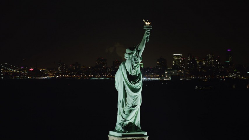 4K aerial  video of orbiting the back of the Statue of Liberty at night, reveal World Trade Center skyline, New York Aerial Stock Footage | AX67_0074