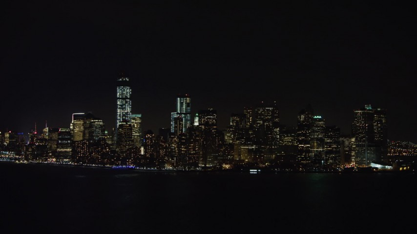 4K stock video aerial view of approaching Lower Manhattan skyline at night, New York Aerial Stock Footage | AX67_0075