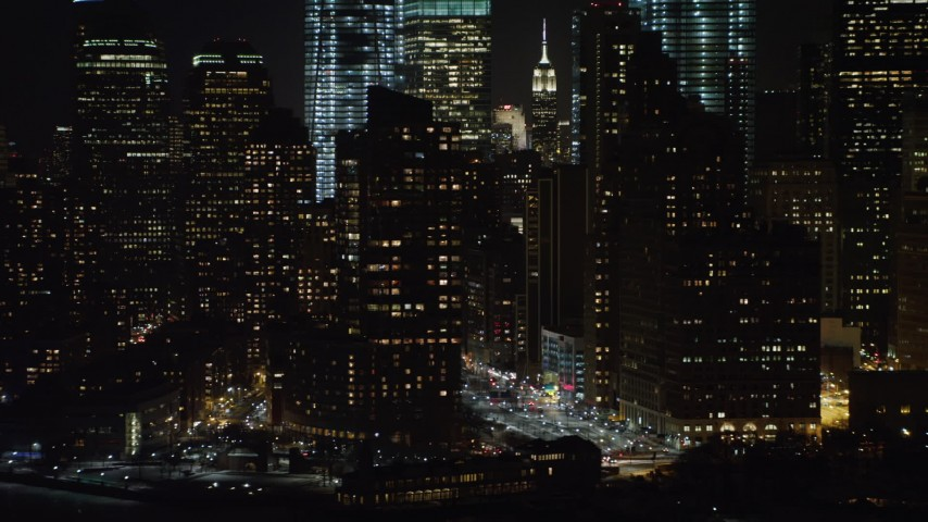 4K stock video aerial view of flying by Lower Manhattan skyscrapers at night, New York Aerial Stock Footage | AX67_0076