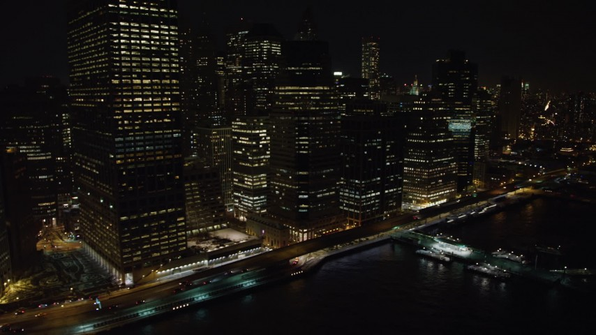 4K stock video aerial view of flying by Lower Manhattan's riverfront skyscrapers at night, New York Aerial Stock Footage | AX67_0077
