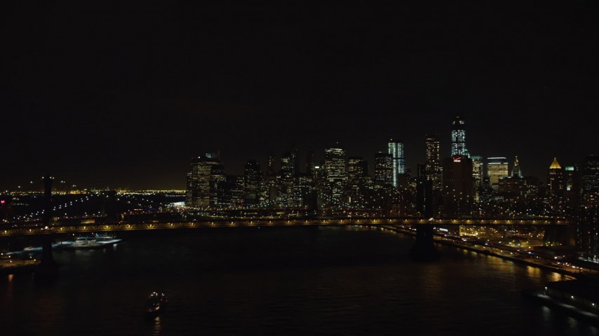 4K stock video aerial view fly over Manhattan Bridge to approach Brooklyn Bridge and Lower Manhattan skyline at night, New York Aerial Stock Footage | AX67_0080
