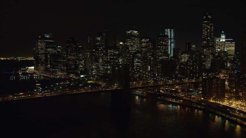 4K stock video aerial view approach the Brooklyn Bridge and Lower Manhattan skyline at night, New York Aerial Stock Footage | AX67_0081