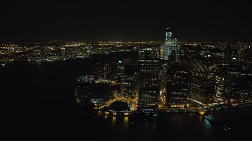 4K stock video aerial view of orbiting Lower Manhattan skyscrapers and Battery Park at night, New York Aerial Stock Footage | AX67_0083