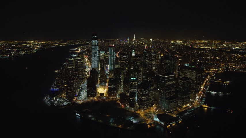 4K stock video aerial view of orbiting Battery Park and Lower Manhattan's tall skyscrapers at night, New York Aerial Stock Footage | AX67_0084