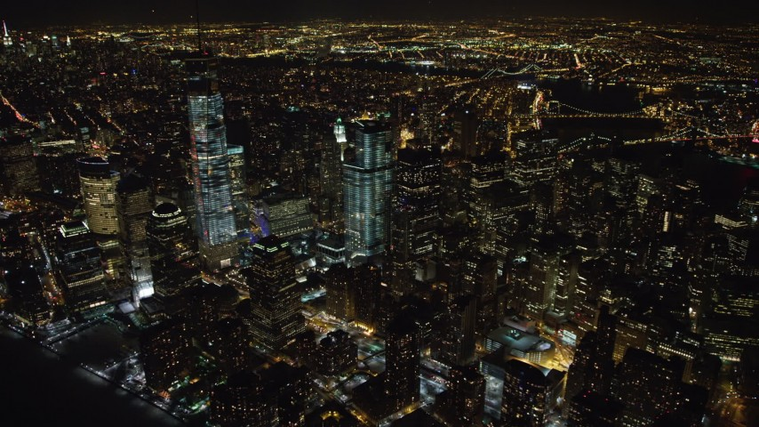 4K stock video aerial view of orbiting tall skyscrapers in Lower Manhattan and the World Trade Center at night, New York Aerial Stock Footage | AX67_0085