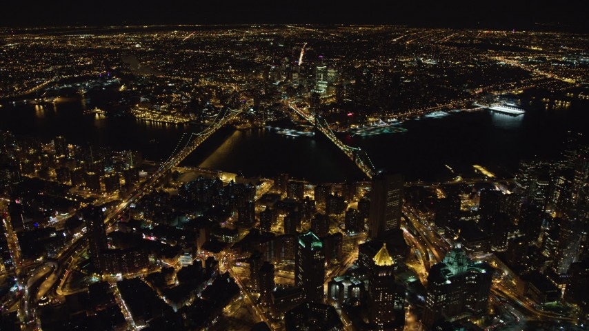 4K stock video aerial view of approaching the Manhattan Bridge and the Brooklyn Bridge at night, New York Aerial Stock Footage | AX67_0087
