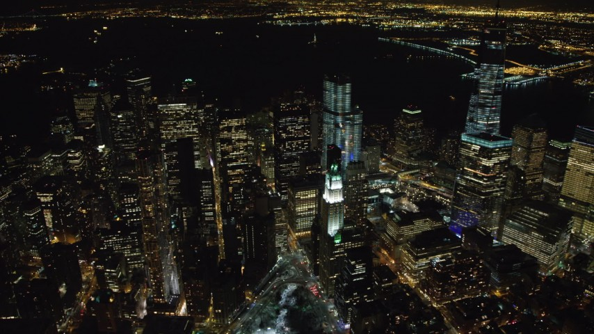 4K stock video aerial view of flying by Lower Manhattan's towering skyscrapers at night, New York Aerial Stock Footage | AX67_0088