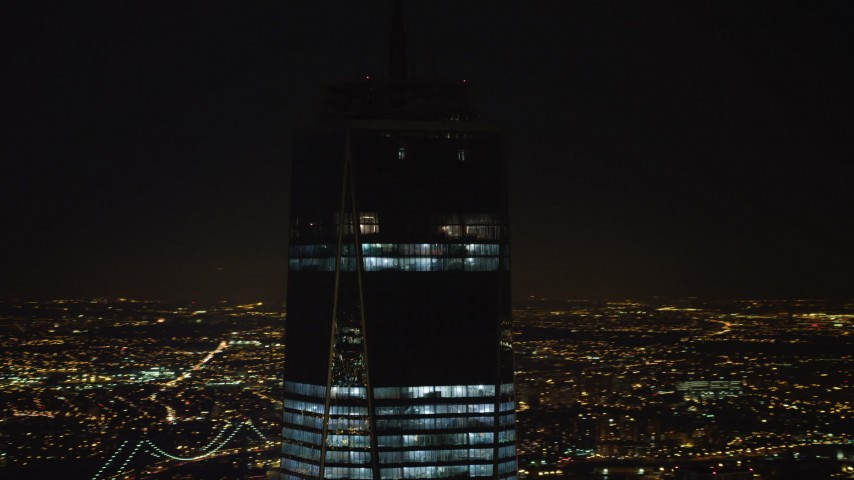 4K stock video aerial view of orbiting top of One World Trade Center at night, Lower Manhattan, New York Aerial Stock Footage | AX67_0091