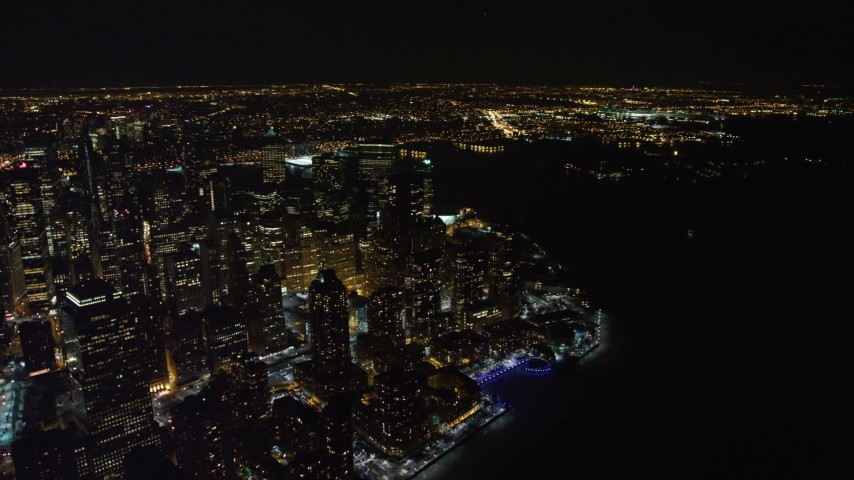 4K stock video aerial view of orbiting skyscrapers by the river in Lower Manhattan at night, New York Aerial Stock Footage | AX67_0093