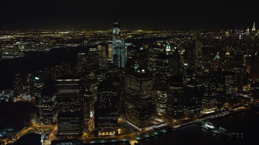 4K stock video aerial view of Lower Manhattan skyscrapers by East River at night, Lower Manhattan, New York Aerial Stock Footage | AX67_0099
