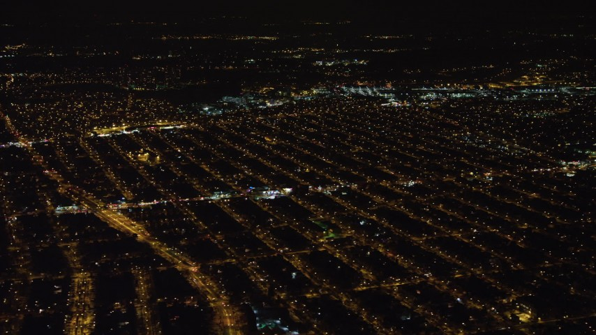 4K stock video aerial view of passing urban neighborhoods in Queens at night, New York Aerial Stock Footage | AX67_0112