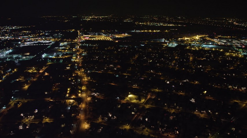 4K stock video aerial view follow Hempstead Turnpike to reveal and approach Republic Airport at night, Long Island, New York Aerial Stock Footage | AX67_0120