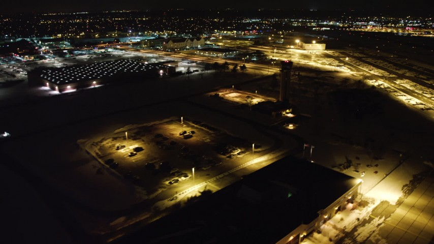 4K stock video aerial view orbit Republic Airport control tower, pan and approach hangars at night, Long Island, New York Aerial Stock Footage | AX67_0121