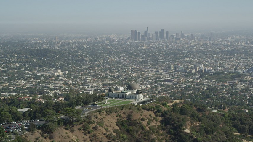 5K stock footage aerial video pass by Griffith Observatory with Downtown Los Angeles in the distance, California Aerial Stock Footage | AX68_005
