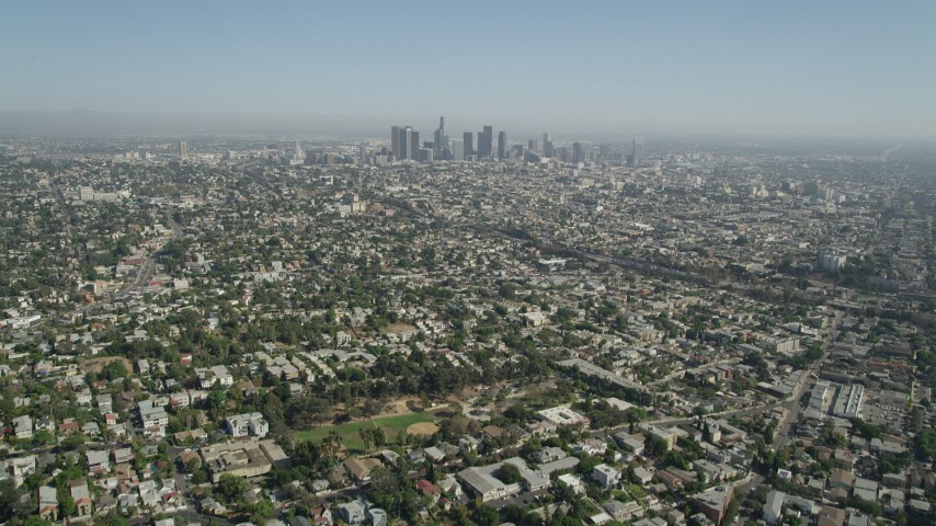 Tilt from urban neighborhoods to reveal Downtown Los Angeles skyline, California Aerial Stock Footage | AX68_009
