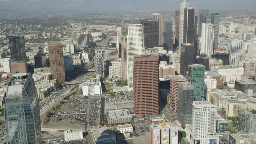 5K stock footage aerial video tilt from Staples Center to reveal and approach Downtown Los Angeles towers, California Aerial Stock Footage | AX68_021