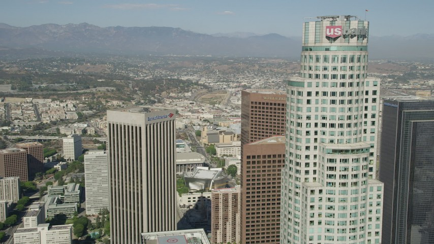Approach the top of US Bank Tower in Downtown Los Angeles, California, and reveal City Hall Aerial Stock Footage | AX68_024
