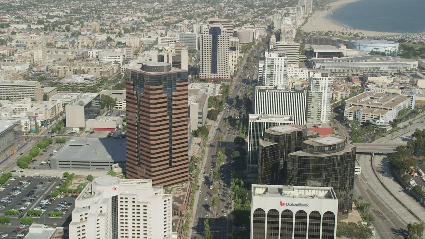 5K stock footage aerial video follow Ocean Boulevard between office buildings in Downtown Long Beach, California Aerial Stock Footage | AX68_055