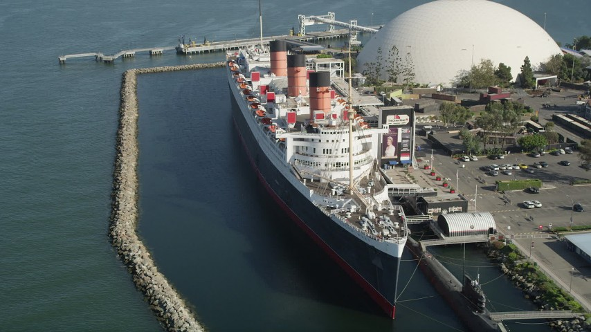5K stock footage aerial video of passing the starboard side of the Queen Mary luxury liner in Long Beach, California Aerial Stock Footage AX68_065 | Axiom Images