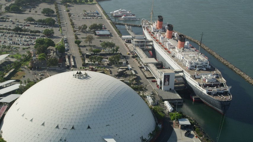5K stock footage aerial video reverse view of the Queen Mary luxury liner and reveal Downtown Long Beach, California Aerial Stock Footage | AX68_068