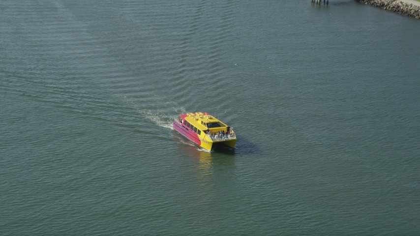 Small yellow and red ferry sailing San Pedro Bay in Long Beach, California Aerial Stock Footage | AX68_073