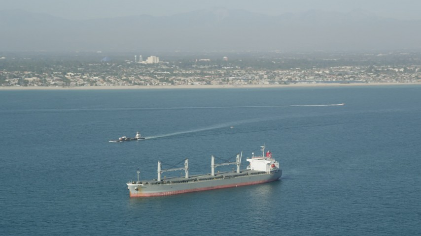 5K stock footage aerial video of a barge sailing near an oil tanker in San Pedro Bay near the coast, Long Beach, California Aerial Stock Footage | AX68_082