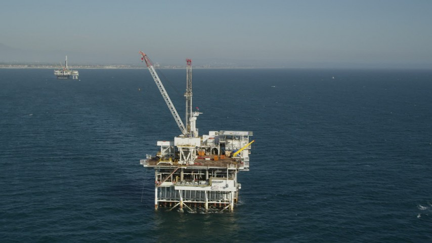 5K stock footage aerial video orbit of an oceanic oil platform with Long Beach in the background, California Aerial Stock Footage | AX68_097