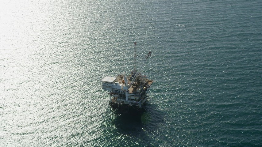 5K stock footage aerial video of an oil drilling platform near sunlight reflected off the ocean near Long Beach, California Aerial Stock Footage | AX68_107