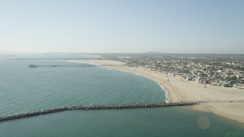 5K stock footage aerial video fly over breakwater to approach the pier by beach and homes, Seal Beach, California Aerial Stock Footage | AX68_122