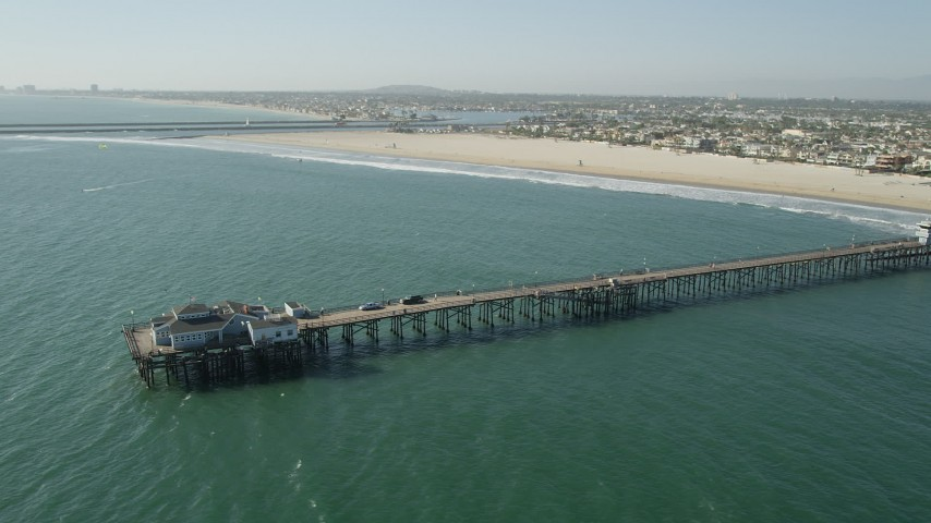 5K stock footage aerial video flyby the end of Seal Beach Municipal Pier by beach and coastal neighborhoods in Seal Beach, California Aerial Stock Footage | AX68_124