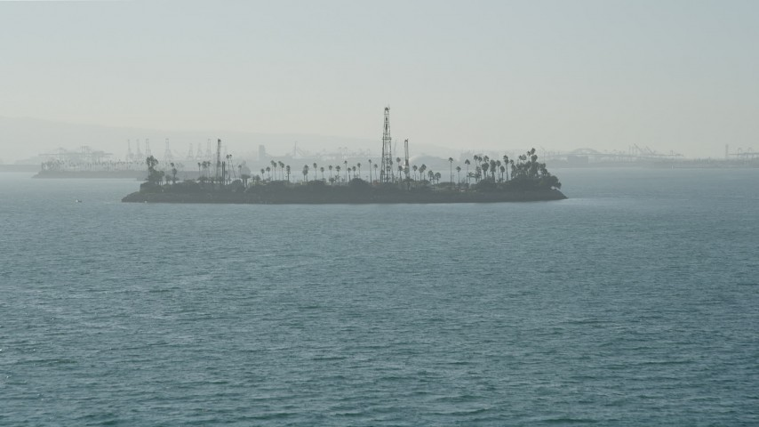 5K stock footage aerial video tilt from San Pedro Bay to reveal Island Chaffee oil island, Long Beach, California Aerial Stock Footage   AX68_125