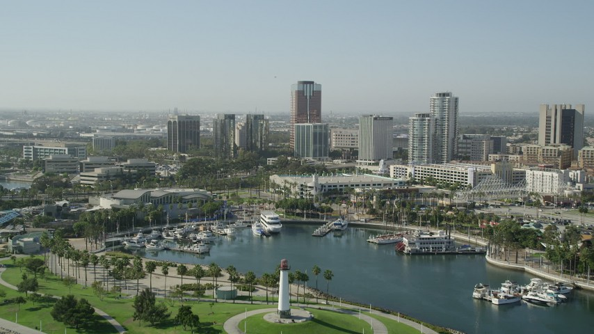 5K stock footage aerial video fly over lighthouse, Shoreline Aquatic Park, and aquarium to approach office buildings in Downtown Long Beach, California Aerial Stock Footage AX68_136