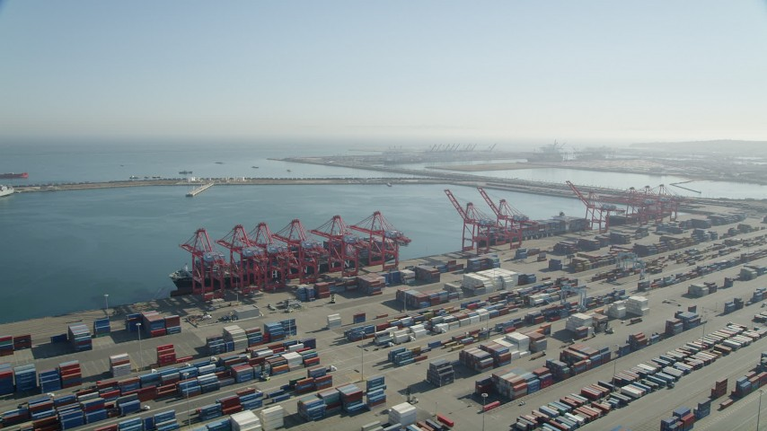 5K stock footage aerial video of cargo ships under cranes near containers at the Port of Long Beach, California Aerial Stock Footage | AX68_143
