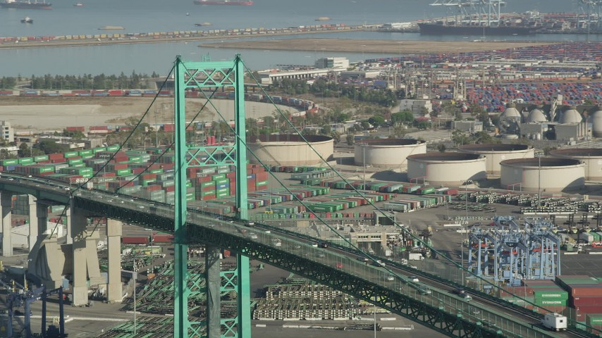 5K stock footage aerial video of passing traffic on Vincent Thomas Bridge by cargo containers at the Port of Los Angeles, California Aerial Stock Footage | AX68_154