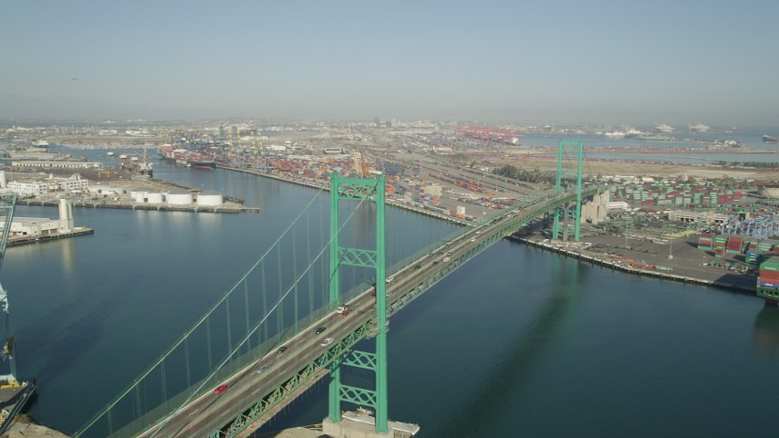 Approach the Vincent Thomas Bridge at the Port of Los Angeles, California and tilt to traffic Aerial Stock Footage | AX68_156