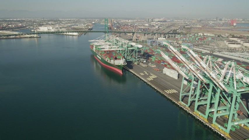 5K stock footage aerial video approach a cargo ship beneath cranes at Port of Los Angeles, California Aerial Stock Footage | AX68_162