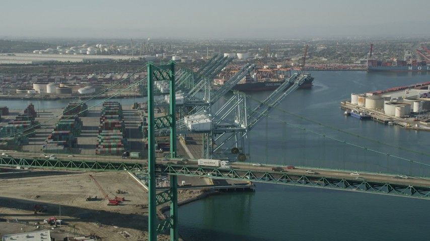 5K stock footage aerial video fly over Vincent Thomas Bridge to approach cranes at the Port of Los Angeles, California Aerial Stock Footage | AX68_164