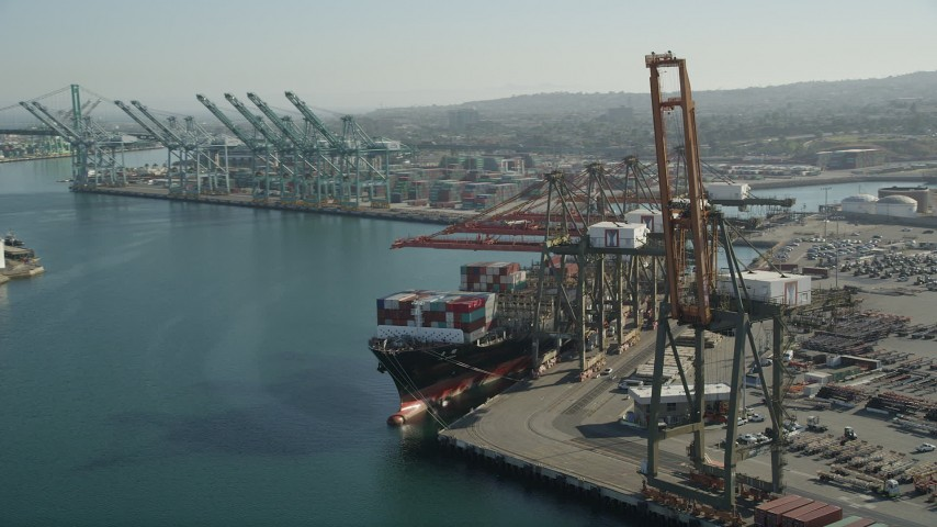 5K stock footage aerial video of passing a cargo ship with containers beneath cranes at the Port of Los Angeles, California Aerial Stock Footage | AX68_170