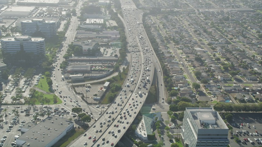 5K stock footage aerial video of heavy traffic on I-405 between office buildings and homes in Torrance, California Aerial Stock Footage | AX68_184