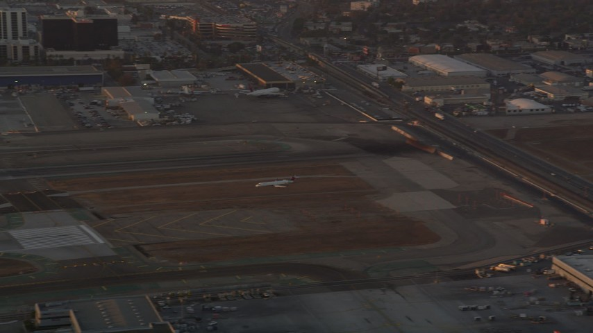 5K stock footage aerial video of tracking an airliner landing on a runway at LAX Airport at sunset, California Aerial Stock Footage | AX69_004