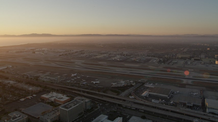 5K stock footage aerial video of sunset at LAX with an airliner on a runway in Los Angeles, California Aerial Stock Footage | AX69_005