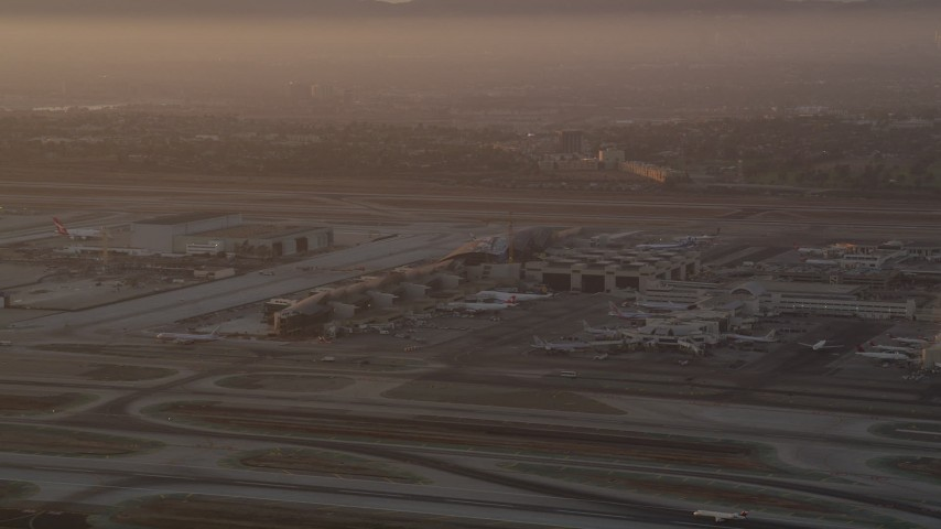 5K stock footage aerial video of terminals, hangars and airliners at LAX at sunset, Los Angeles, California Aerial Stock Footage | AX69_006