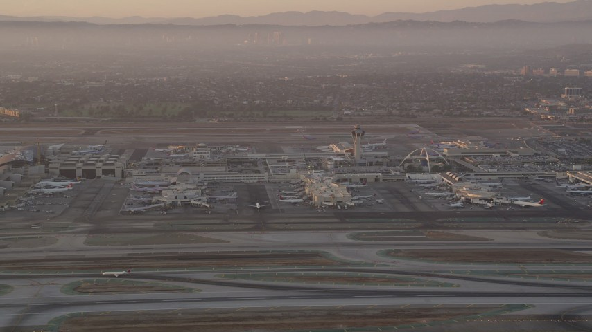 5K stock footage aerial video of terminals and control tower at LAX at sunset, Los Angeles, California Aerial Stock Footage | AX69_007