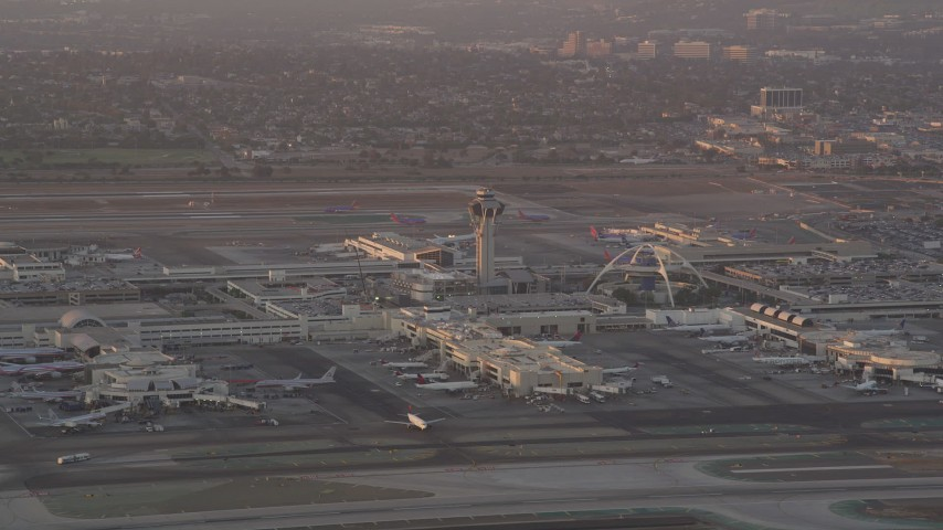 5K stock footage aerial video of LAX control tower and terminals as airliner lands at sunset, Los Angeles, California Aerial Stock Footage | AX69_008