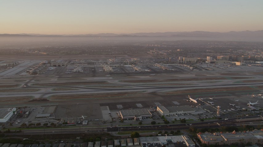 5K stock footage aerial video of a view of runways, terminals and hangars at LAX at twilight, Los Angeles, California Aerial Stock Footage | AX69_009