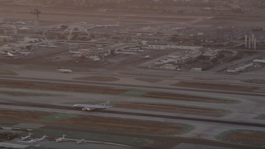5K stock footage aerial video track airliner on runway and tilt to reveal control tower and terminals at LAX at twilight, Los Angeles, California Aerial Stock Footage | AX69_012