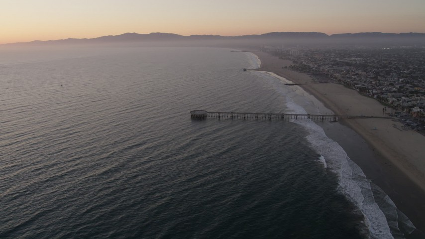 Approach the Venice Fishing Pier on the coast at sunset, California Aerial Stock Footage | AX69_024