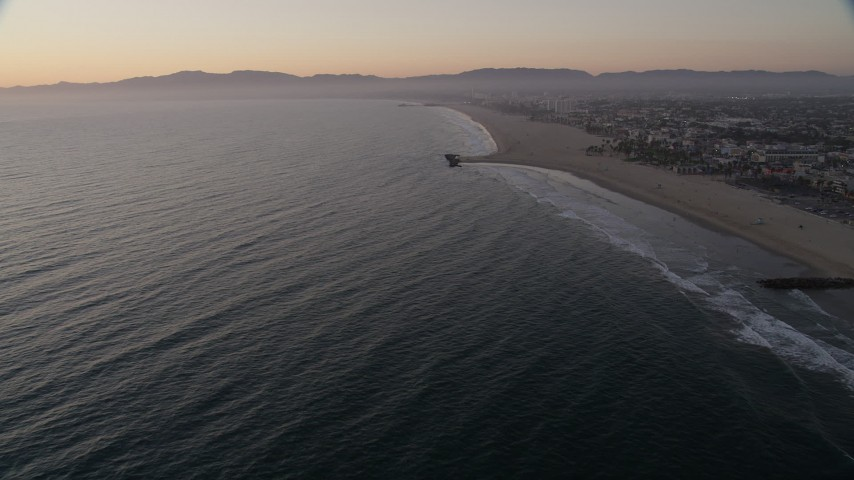 Tilt to reveal Venice Fishing Pier and empty beach to Santa Monica at sunset, California Aerial Stock Footage | AX69_025